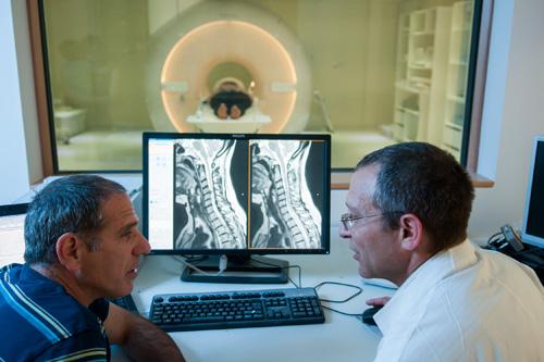 """פרופ' אלון פרידמן וד""""ר אילן שלף על רקע מכשיר ה-fMRI בסורוקה (צילום: דני מכליס. התמונה באדיבת דוברות סורוקה ואונ' בן-גוריון)"""